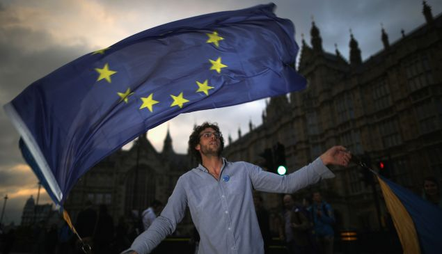 LONDON, ENGLAND - JUNE 28: A protester waves an EU flag in front of the Houses of Parliament as they demonstrate against the EU referendum result on June 28, 2016 in London, England. Up to 50,000 people were expected before the event was cancelled due to safety concerns. Early evening up to 2000 people have still converged on the square and then marched to Parliament to vent their anti-Brexit feelings.