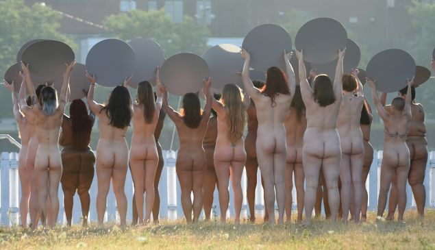 "Women holding mirrors participate in a photo shoot by artist Spencer Tunick in his latest large-scale art installation: Everything She Says Means Everything,"" across from site of the Republican National Convention in Cleveland July 17, 2016 where naked women will stand facing the Quicken Loans Arena holding large, round mirrors. / AFP / TIMOTHY A. CLARY / RESTRICTED TO EDITORIAL USE - MANDATORY MENTION OF THE ARTIST UPON PUBLICATION - TO ILLUSTRATE THE EVENT AS SPECIFIED IN THE CAPTION - NO CLOSE UP SHOTS TO BE REPRODUCED OF INDIVIDUALS INVOLVED IN THE INSTALLATION"