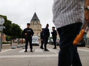 A man carries a French baguette as police officers stand guard the Saint-Etienne church on July 27, 2016 in Saint-Etienne-du-Rouvray, 125 kilometres (77 miles) north of Paris, where a priest was killed the day before in the latest of a string of attacks against Western targets claimed by or blamed on the Islamic State jihadist group. Father Jacques Hamel, a semi-retired assistant parish priest, had his throat slit in a church in northern France on July 26, 2016, after two men stormed the building and took hostages. As the two attackers made to leave the church they were confronted by a French police unit specialising in hostage situations, the BRI, and were shot dead.
