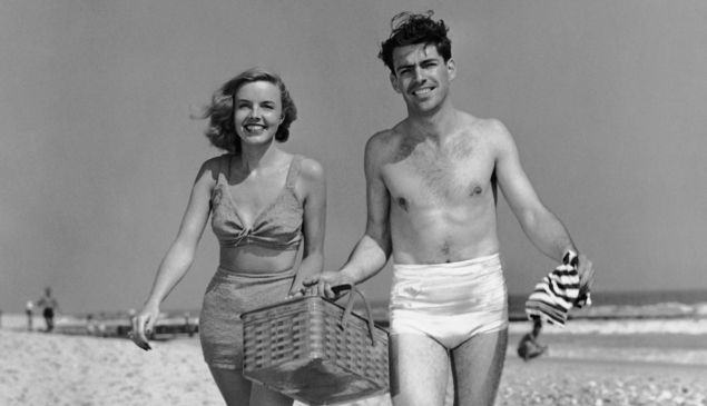UNITED STATES - CIRCA 1950s: Couple walking with picnic basket on beach.