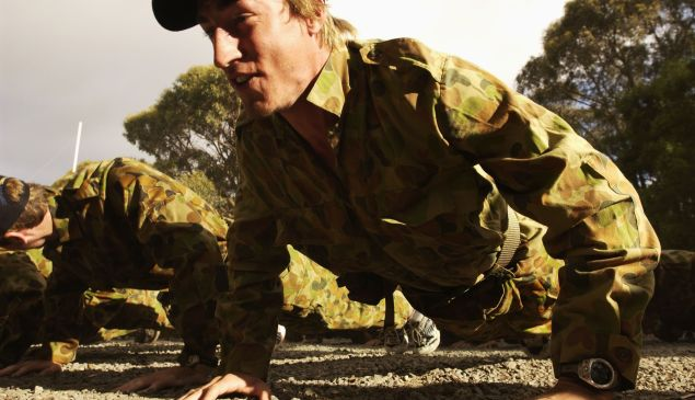BALLARAT, AUSTRALIA - DECEMBER 4: Clint Bizell does push ups during a commando training session at the Melbourne Demons AFL Football Club pre season training camp at the Pax Scout Camp, Ballarat, Australia on December 4, 2002.