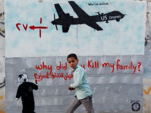 A boy walks past graffiti denouncing strikes by U.S. drones in Yemen, painted on a wall in Sanaa, Yemen.