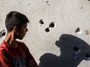 "A boy stands near impacts of projectile on a wall near the explosion scene in Gaziantep in southeastern Turkey near the Syrian border on August 21, 2016. Turkish President Recep Tayyip Erdogan on Sunday said the Islamic State (IS) group was the ""likely perpetrator"" of the bomb attack."