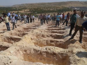 """People wait close to empty graves at a cemetery during the funeral for the victims of last night's attack on a wedding party that left 50 dead in Gaziantep in southeastern Turkey near the Syrian border on August 21, 2016. At least 50 people were killed when a suspected suicide bomber linked to Islamic State jihadists attacked a wedding thronged with guests, officials said on August 21. Turkish President Recep Tayyip Erdogan said the IS extremist group was the """"likely perpetrator"""" of the bomb attack, the deadliest in 2016, in Gaziantep late Saturday that targeted a celebration attended by many Kurds."""