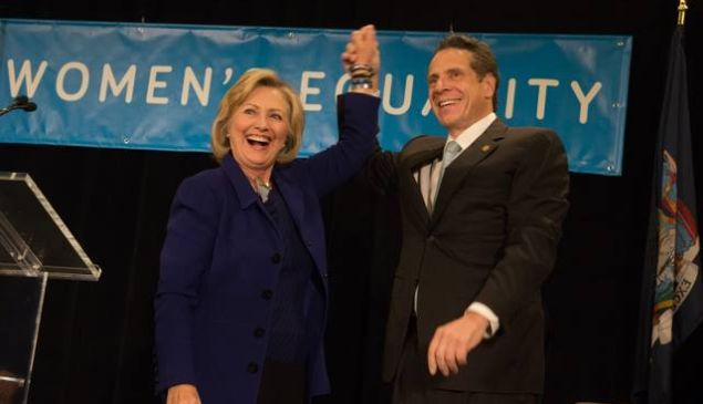 Hillary Clinton and Andrew Cuomo pose in front of a Women's Equality Party banner.