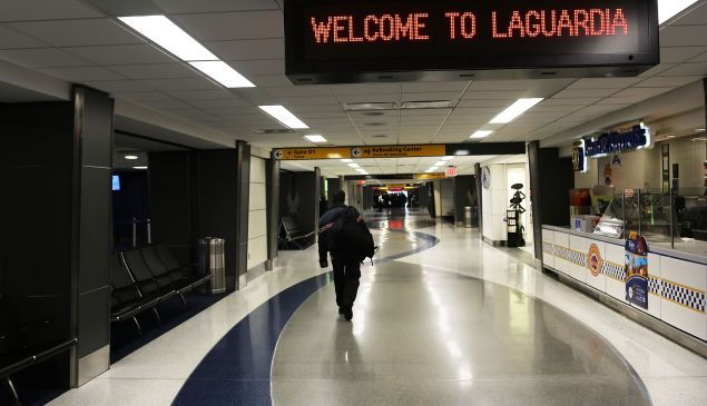 A lone person walks through an empty LaGuardia Airport (Photo by Spencer Platt/Getty Images)