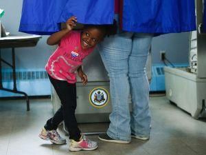 A young girl looks out of a voting booth during Pennsylvania's primary election on April 26, 2016 in Philadelphia, Pennsylvania.