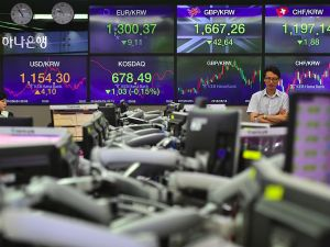 Currency dealers monitor exchange rates in front of screens showing exchange rates for Korean won against the Pound and the Euro (C top) in a trading room at the KEB Hana Bank in Seoul on June 24, 2016. South Korean shares turned lower in late morning on June 24, as the results of the British referendum remain murky.