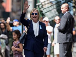 "TOPSHOT - US Democratic presidential nominee Hillary Clinton waves to the press as she leaves her daughter's apartment building after resting on September 11, 2016, in New York. Clinton departed from a remembrance ceremony on the 15th anniversary of the 9/11 attacks after feeling ""overheated,"" but was later doing ""much better,"" her campaign said. / AFP / Brendan Smialowski"