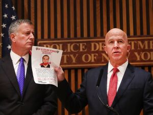New York City police commissioner James O'Neill stands with Mayor Bill de Blasio as he holds up a picture of Ahmad Khan Rahami, the man believed to be responsible for the explosion in Manhattan on Saturday night and an earlier bombing in New Jersey, at a news conference at New York City on September 19, 2016 in New York City. Rahami was taken into custody on Monday afternoon.
