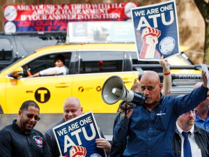 A New York City taxi cab drives by as Syed Manzar, who drives for both Uber and Lyft, speaks during a rally to call on the New York City Taxi and Limousine Commission to force Uber and Lyft to hold union elections, September 27, 2016 in the Queens borough of New York City.