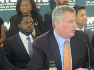 Mayor Bill de Blasio announces a new vision for the city's MWBE program, with his senior MWBE adviser, Rev. Jonnel Doris, behind him.