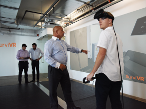 Background: Human Condition Safety Founders, Oliver Rothauser and Peter Raymond. Center: Lorenzo Gallo, CEO of the Safety Group, demonstrating a virtual reality training.