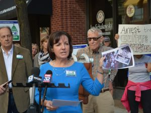 Republican congressional candidate Joan McCarthy Lasonde at a press conference in front of incumbent Jan Schakowsky's district office in downtown Evanston. Lasonde demanded that Schakowsky resign based on her alleged complicity in what Lasonde referred to as 'orchestrated political violence.' The photo she's holding shows Schakowsky at a rally outside the Governor's Dinner in downtown Chicago holding up the 'Gang of Hate' sign printed by her husband's subcontractors at Americans United for Change.