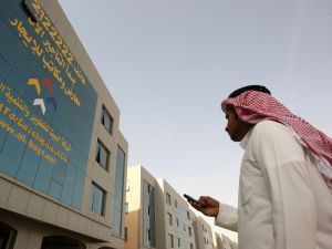 TO GO WITH AFP STORY BY PAUL HANDLEYA Saudi man takes the number of a real estate company from the facade of a building on King Fahd road in the Saudi capital Riyadh on December 14, 2010 where one office building after another sports a gigantic telephone number: the international sign of a desperate search for tenants. AFP PHOTO/HAMAD OLAYAN