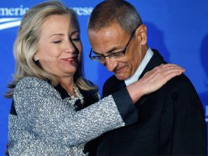 "U.S. Secretary of State Hillary Clinton (L) embraces Center for American Progress President and CEO John Podesta before addressing the centers' ""American Idea: A More Perfect Union"" conference at the Decatur House October 12, 2011 in Washington, DC."