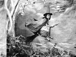circa 1865: A young girl dressed as a witch suspended mid-air on a broomstick.