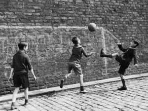 A group of boys playing soccer in the street in Salford, Lancashire.