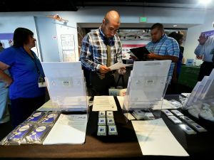 Albert Dorado (C), who served in the Marines, looks over forms while attending the first Los Angeles International Airport (LAX) Job Fair for Veterans in Los Angeles, California on September 14, 2016.