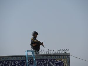 An Afghan policeman keeps watch inside the Karte Sakhi shrine in Kabul on October 12, 2016, after an attack by gunmen late on October 11. Grieving worshippers on October 12 described desperately trying to shelter their children against a hail of gunfire in Kabul that killed at least 18 people gathering to mark Ashura, one of the most important festivals of the Shiite calendar. / AFP / SHAH MARAI