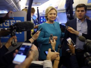 Democratic presidential nominee former Secretary of State Hillary Clinton speaks to reporters on her campaign plane while traveling from Tampa, Florida to New York on October 26, 2016.