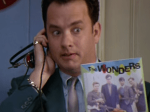 Tom Hanks using a prehistoric iPhone to listen a floppy disk (I presume).