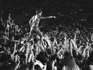 Iggy Pop of the Stooges rides the crowd during a concert at Crosley Field on June 23, 1970 in Cincinnati, Ohio.