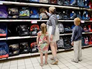 A mother and her children look at the range of school supplies in a supermarket of Englos, northern France, on July 9, 2013, ahead of the start of the classes in September. AFP PHOTO/ DENIS CHARLET (Photo credit should read DENIS CHARLET/AFP/Getty Images)