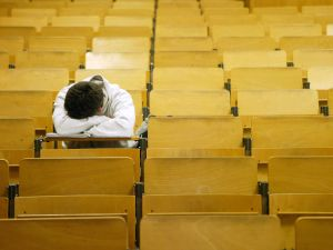 A student naps in a lecture hall.