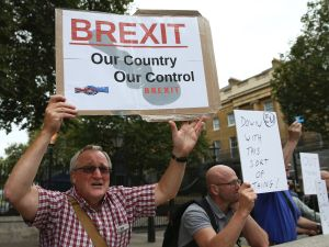 A man carrying an anti-EU pro-Brexit placard joins a counter protest against pro-Europe marchers on a March for Europe demonstration against the Brexit vote in Parliament Square in central London on September 3, 2016.