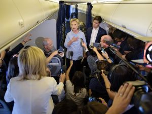 Democratic presidential nominee Hillary Clinton speaks to the press onboard her plane September 5, 2016 above Iowa.