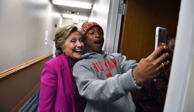 Democratic presidential nominee Hillary Clinton poses with singer Pharrell Williams for a selfie backstage before a campaign rally in Raleigh, North Carolina, on November 3, 2016. / AFP / JEWEL SAMAD (Photo credit should read JEWEL SAMAD/AFP/Getty Images)