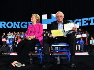 US Democratic presidential nominee Hillary Clinton and Bernie Sanders listen to singer Pharrell Williams during a campaign rally in Raleigh, North Carolina, on November 3, 2016.