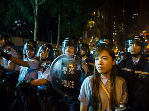 Yau Wai-ching of the stands in front of riot police amid ongoing protests in Hong Kong. China has blocked Yau from taking her elected seat in Hong Kong's legislature for her separatist beliefs.
