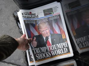 LONDON, ENGLAND - NOVEMBER 09: A man picks up a copy of London's Evening Standard newspaper featuring a photograph and story about U.S President-elect Donald Trump on the front page, on November 9, 2016 in London, England. The American public voted the Republican candidate Donald Trump to be the 45th President of the United States. After 46 of the 50 states results were counted he had 278 of the 538 electoral college votes and Hillary Clinton conceded defeat in a telephone call. British Prime Minister Theresa May congratulated Trump releasing a statement promising to work with him to build on the special relationship between the UK and the USA.