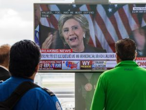 People walking at Ronald Reagan National Airport airport gather around a television monitor and watch US Democratic nominee Hillary Clinton deliver her concession speech November 9, 2016, a day following the election that US Republican nominee Donald Trump won in Arlington, Virginia. / AFP / PAUL J. RICHARDS