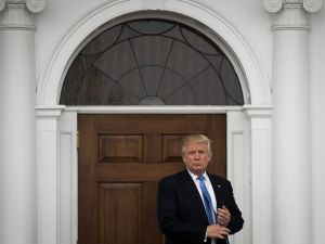 President-Donald Trump stands outside the clubhouse at Trump National Golf Club.