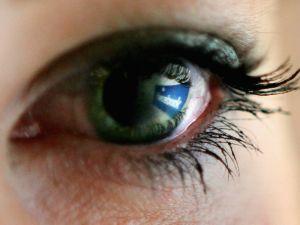 Facebook logo is reflected in an eye.