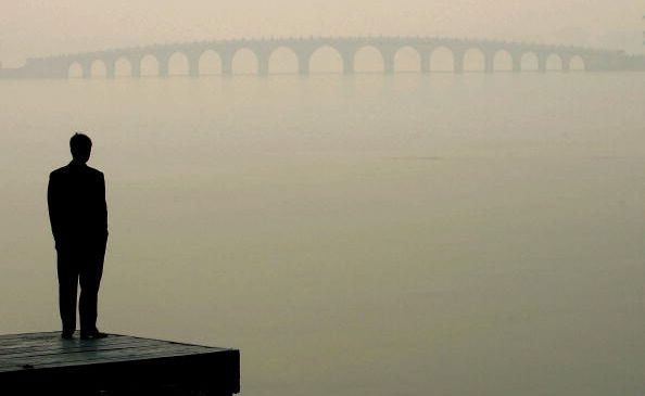 A man looks towards a bridge in heavy fog on December 14, 2004 in Beijing, China.