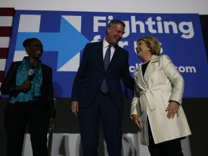 Mayor Bill de Blasio flanked by his wife Chirlane McCray and by Hillary Clinton.