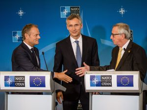 President of the European Council Donald Tusk (L) shakes hand with President of the European Commission Jean-Claude Juncker (R) in front of NATO Secretary General Jens Stoltenberg (C) during a joint press conference after signing the EU-NATO Joint Declaration at the NATO summit in Warsaw, Poland, on July 8, 2016.