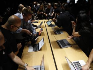 Members of the media gather around a table displaying the new Apple MacBook Pro laptop after the product launch event on October 27, 2016 in Cupertino, California.