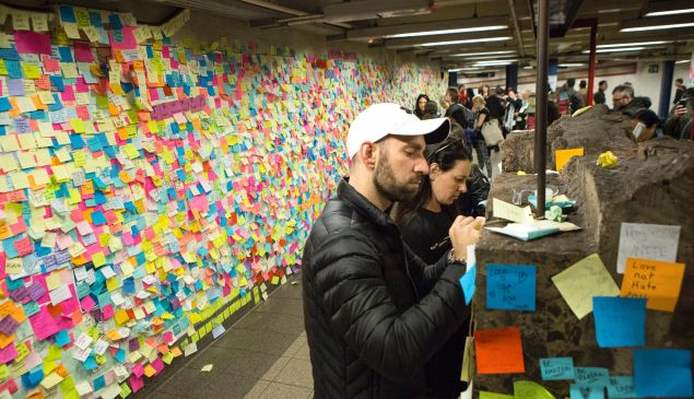 """People stick a Post-It note to participate in the art piece 'Subway Therapy' at the Union Square subway station in New York on November 17, 2016 """"Subway Therapy"""" allows people to express their thoughts with the public, and began after the November 8, 2016 US presidential election."""