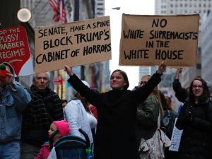 A woman protests against US President-elect Donald Trump in front of Trump Tower on November 20, 2016 in New York. / AFP / KENA BETANCUR