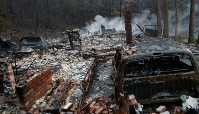 GATLINBURG, TN - NOVEMBER 30: The remains of a home smolder in the wake of a wildfire November 30, 2016 in Gatlinburg, Tennessee. Thousands of people have been evacuated from the area and over 100 houses and businesses were damaged or destroyed. Drought conditions and high winds helped the fire spread through the foothills of the Great Smoky Mountains.