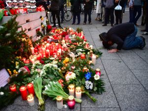 A Muslim mam prays at a makeshift memorial for the attack victims, on December 20, 2016 in front of the Kaiser-Wilhelm-Gedaechtniskirche (Kaiser Wilhelm Memorial Church) in Berlin, where a truck crashed into a Christmas market. Twelve people were killed and almost 50 wounded, 18 seriously, when the lorry tore through the crowd on December 19, 2016, smashing wooden stalls and crushing victims, in scenes reminiscent of July's deadly attack in the French Riviera city of Nice. / AFP / John MACDOUGALL