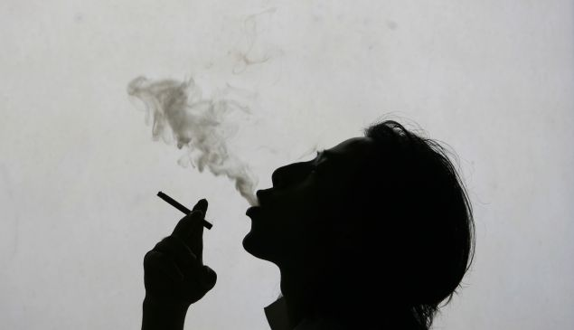 A man exhales smoke whilst smoking a cigarette on World No Tobacco Day.