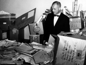 John Glenn stands in the NASA mail room surrounded by thousands of letters sent to him.