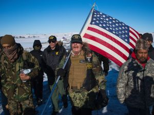 US Navy deep sea diving veteran Rob McHaney (C) holds an American flag as he leads a group of veteran activists back from a police barricade on a bridge near Oceti Sakowin Camp on the edge of the Standing Rock Sioux Reservation on December 4, 2016 outside Cannon Ball, North Dakota.