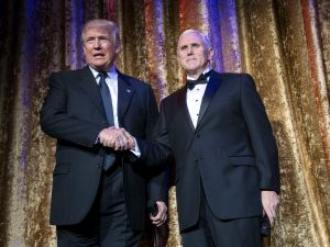 WASHINGTON, DC - JANUARY 17: President-elect Donald Trump (L) and Vice President-elect Mike Pence arrive on stage at the Chairman's Global Dinner, at the Andrew W. Mellon Auditorium on January 17, 2017 in Washington, DC. The invitation-only black-tie event offered an opportunity for Trump to introduce himself and members of his cabinet to foreign diplomats.